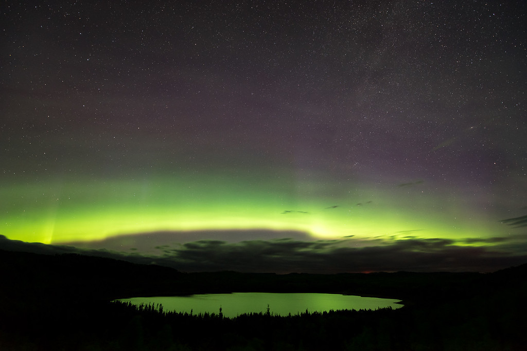 "MONDAY, JUNE 6, 2016<br /> <br /> AURORA 8070<br /> <br /> ""Aurora Arc over Teal Lake""<br /> <br /> Here is another photo from last night's aurora surprise.  After watching the lights dancing over the pond, we headed back down towards the village with the intent of going home for the night.  As we drove back, however, the lights looked like they might be picking back up in intensity so we decided to head to one more location before calling it a night.  <br /> <br /> The lake shown in this photo is called Teal Lake and is easily visible from Highway 61 in Grand Portage, MN.  It makes for a great spot to watch the northern lights as it is an elevated viewpoint with nothing to block the view of the northern sky.  We only had a short time to enjoy the aurora from here, though.  As you can see beneath the arc of light, there is a cloud bank that was fast approaching from the northeast.  It didn't take long for these advancing clouds to obscure the view of the lights.  It was probably a good thing, however, as we both had to be up early in the morning.  Once the clouds blocked the view we called it a night and headed home.<br /> <br /> Camera: Nikon D750<br /> Lens: Nikon 14-24mm f/2.8<br /> Focal length: 14mm<br /> Shutter speed: 15 seconds<br /> Aperture: f/2.8<br /> ISO: 1600"