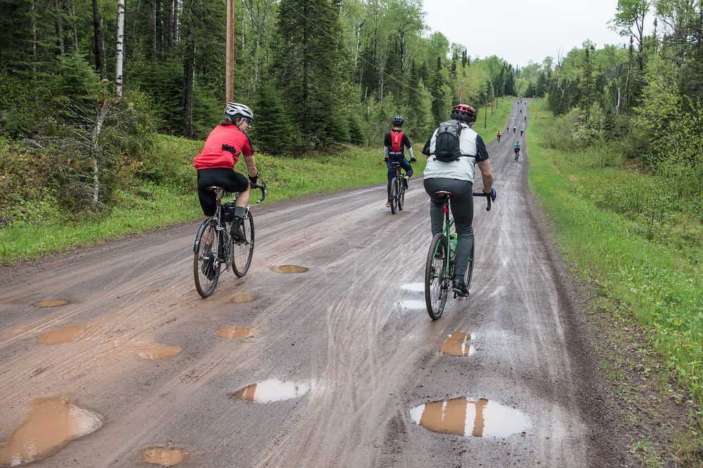 "SUNDAY, MAY 29, 2016<br /> <br /> BIKING 00467<br /> <br /> ""Le Grand du Nord - May 28, 2016""<br /> <br /> Yesterday Jessica and I rode in ""Le Grand du Nord"", a bike event/race starting and ending in Grand Marais, MN.  There was a 50 mile ride and a 100 mile ride; we participated in the 50.  This was my first time ever participating in something like this and I had a blast!  After the rain the night before the course was pretty wet but still lots of fun.  The temperature was actually kind of perfect.  All of the riders were super friendly.  It was a lot of fun chatting with fellow riders as we rode along and interesting to see the huge variety of bikes and setups that people were using.  The course was roughly 90% on gravel roads, with just a couple of short pavement sections and only one short section that was really rough.  Very well designed and challenging route with 3,000 feet of climbing.  Thanks to all those involved in planning and implementing this event... we sure had a great time!  And, of course, you know me... I just had to bring a camera along!  A few people poked fun at me for taking pictures during a bike race, but whatever... I had loads of fun and now I have some cool pictures to go with my memories of the day!<br /> <br /> In this photo riders are nearing the top of the climb on Lindskog Road, just before turning east on County Road 60.<br /> <br /> Camera: Sony DSC-RX100M3<br /> Focal length: 45mm<br /> Shutter speed: 1/500<br /> Aperture: f/4<br /> ISO: 400"