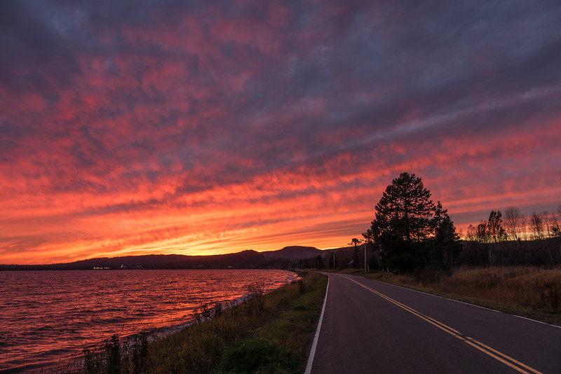 "TUESDAY, NOVEMBER 8, 2016<br /> <br /> GRAND PORTAGE 03132<br /> <br /> ""November Sunset over the Bay Road""<br /> <br /> A surprise sunset that turned out awesome last night!  I was driving home from work and it looked like sunset was going to be a bust.  Since the sky was so full of clouds I figured it would just be gray. But lo and behold, as soon as I pulled in my driveway the sky started to light up.  I grabbed the camera and walked 1/4 mile back down the road to make this photograph. <br /> <br /> Camera: Sony DSC-RX10M3<br /> Focal length: 24mm<br /> Shutter speed: 1/20<br /> Aperture: f/4<br /> ISO: 64"