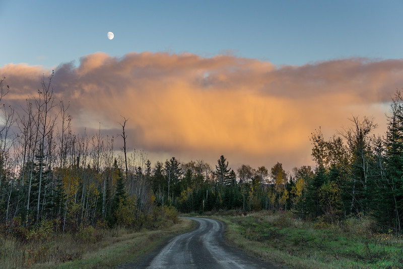 """THURSDAY, OCTOBER 13, 2016<br /> <br /> FOREST 02287<br /> <br /> """"October Moon, Otter Lake Road""""<br /> <br /> Yesterday after a fun 15 mile combination hiking/biking loop I was driving home via the Otter Lake forest road and there were beautiful rain/snow squalls occurring all around the horizon.  Many of the clouds were lit up beautifully by the setting sun. As I rounded a curve in the road this scene was laid out before me, with the rising moon just above one of the squalls.  It sure was a great ending to a fun day of adventure in the Minnesota north woods!<br /> <br /> Camera: Sony DSC-RX10M3<br /> Focal length: 68mm<br /> Shutter speed: 1/320<br /> Aperture: f/3.5<br /> ISO: 100"""