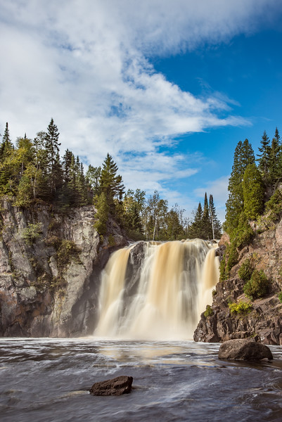 "SUNDAY, OCTOBER 2, 2016<br /> <br /> RIVERS 0166<br /> <br /> ""High Falls, Tettegouche State Park""<br /> <br /> Last week I had to go to Duluth for a few things so I decided to head down in the evening and spend the night at my brother's place.  That way I could get my errands done in the morning and do some hiking in the afternoon on the way home.  I really wanted to hike to the waterfalls at Tettegouche Stat Park.  When the morning rolled around, however, the weather was not looking promising.  It was raining all morning and when I started driving back up the shore it was raining there as well.  I really didn't feel like hiking in the rain so I was beginning to think I wasn't going to get a hike in.  <br /> <br /> Lucky for me, just before arriving at Tettegouche State Park the rain stopped and some breaks in the clouds started to appear.  I figured I'd make a run for it.  Maybe I'd get lucky and I could see the waterfalls while dodging any further rain storms.  For the next couple of hours my luck held out and I was able to hike to both High Falls and Two Step Falls without any rain falling.  I even had some nice sunlight for a few moments at each waterfall.  When I got back to my car and resumed my drive up the shore, it wasn't long before it started raining again!  What luck I had on this day to make the hike in between rain showers and to have just enough sunlight on the waterfalls to make a mid-day shot more interesting :-)<br /> <br /> Camera: Nikon D750<br /> Lens: Nikon 24-120mm f/4<br /> Focal length: 48mm<br /> Shutter speed:  1.3 seconds<br /> Aperture: f/22<br /> ISO: 100"