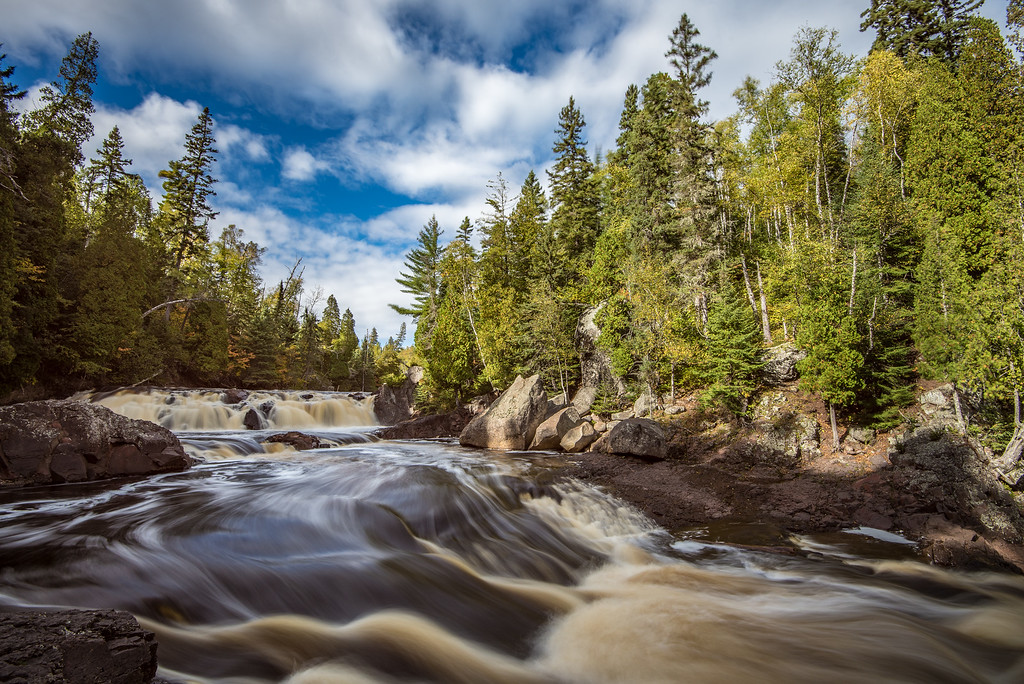 "SUNDAY, OCTOBER 2, 2016<br /> <br /> RIVERS 0189<br /> <br /> ""Two Step Falls, Baptism River""<br /> <br /> Luck was on my side during my visit to Tettegouche State Park last week.  Most of the week our skies were dominated by two things: thick, gray clouds and rain.  For the two hours I was hiking at Tettegouche, however, the clouds did part for a while.  When the clouds parted some nice mid-afternoon sunlight came through and illuminated the trees on the far side of the river.  I ended up with a really nice sky and some nice light for this photo.  As soon as I left the park, the clouds moved back in and it was cloudy again for the rest of the day.<br /> <br /> Camera: Nikon D750<br /> Lens: Nikon 16-35mm f/4<br /> Focal length: 16mm<br /> Shutter speed:  1 second<br /> Aperture: f/16<br /> ISO: 100"