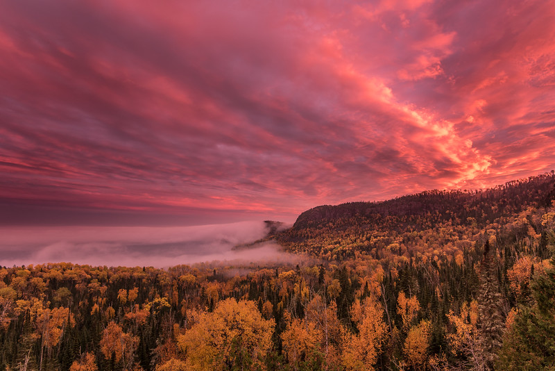 """SUNDAY, OCTOBER 16, 2016<br /> <br /> SUPERIOR FALL 0735<br /> <br /> """"Sky on Fire""""<br /> <br /> On the way home from work last night I witnessed probably the best sunset I've seen so far this year.  It was a complete surprise too.  When I left work it was totally foggy and I couldn't even see the sky.  Everything was gray.  As I drove south on Highway 61 and started to climb the Mt. Josephine grade, the fog started to thin and soon I could see the sky.  It looked like the color was just about to get really good so I pulled into the Mt. Josephine wayside to make some photos.  Jut moments after I got out of the car with my camera the sky lit up like it was on fire.  The color was unbelievable.  It made for quite a surreal view along with the autumn colors in the trees and the fog over Lake Superior.  What a great way to end the day!<br /> <br /> Camera: Nikon D750<br /> Lens: Nikon 16-35mm f/4<br /> Focal length: 16mm<br /> Shutter speed: 0.4 seconds<br /> Aperture: f/11<br /> ISO: 200"""