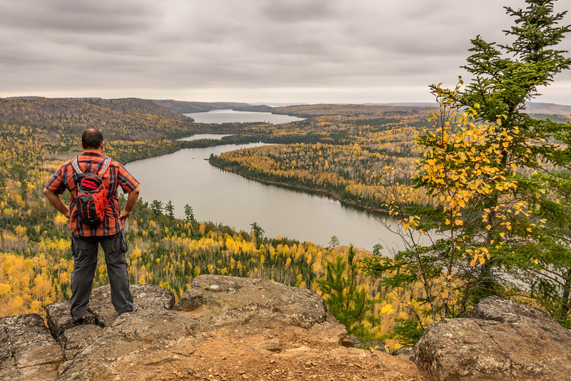"""FRIDAY, OCTOBER 14, 2016<br /> <br /> AUTUMN 02162<br /> <br /> """"Autumn Paradise, Border Route Trail""""<br /> <br /> On my first day off this week I went for a 12 mile hike on the South Lake Trail and Border Route Trail.  For years I've heard about and seen photos from the overlooks along this section of trail.  The photos showed spectacular views overlooking several lakes along the U.S./Canada border.  Ever since the first time I've seen those photos I've wanted to see those views for myself.  I always thought they involved a definite overnight backpack or several day trip via canoe.  Well, recently I started looking into it a bit more since I've been doing a lot of hiking.  I found out that it was probably a round-trip hike in the distance of 12 to 14 miles.  With all the hiking I've done in the last couple of months I figured that was possible as a long day hike.  <br /> <br /> So, on Tuesday I got an early start and after 3 hours of hiking (I could have done it in a little less than that but you know me... I was stopping and taking quite a few photos along the way) I was standing at this overlook.  The view is to the west and overlooks West Rose Lake, Rat Lake and South Lake.  It was an unbelievably calm day.  I couldn't believe that there wasn't even the faintest hint of a breeze on this high spot overlooking these beautiful lakes.  At one point I even saw a couple of swans swimming along the shoreline of Rose Lake.  I couldn't believe how nice of a day it was.  All I was missing was some sunshine and blue sky.  Even without that, the view was incredible.  Easily one of the best overlook views in Minnesota. <br /> <br /> When I got back to my car, my GPS was showing a round-trip distance of exactly 12.0 miles with an elevation gain of just over 2,000 feet.  I was pretty tired but didn't feel beat the way I did after hiking the Caribou Rock Trail.  That trail is east of the South Lake Trail and also goes to Rose Lake, but quite a bit further east along the lake.  """
