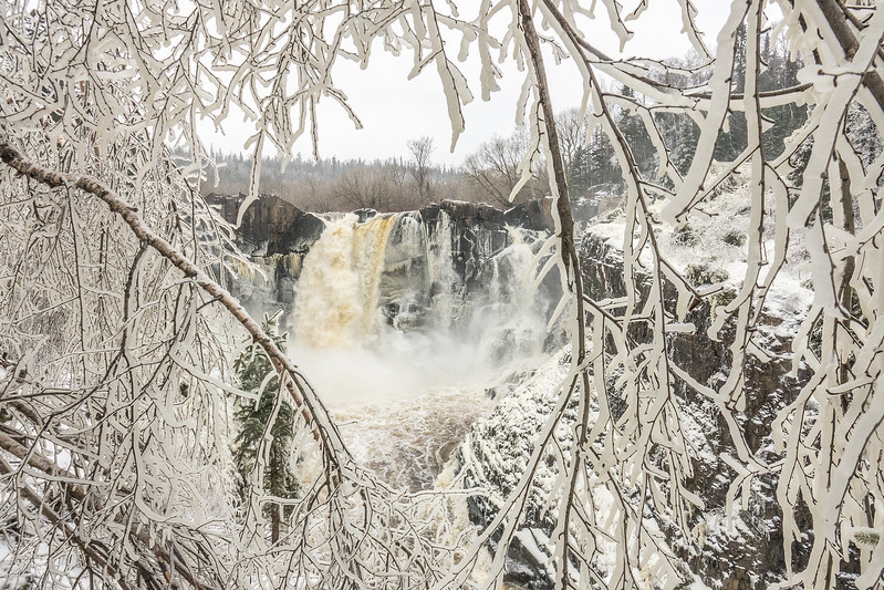 "FRIDAY, APRIL 28, 2017<br /> <br /> PIGEON RIVER 03827<br /> <br /> ""High Falls through a Window of Ice""<br /> <br /> Grand Portage State Park, MN - Fascinating conditions right now at High Falls, thanks to the ice and snow storm we just had over the past couple of days.  Once again we are subjected to the beauty of winter!  Only it's not winter... right?<br /> <br /> Camera: Sony DSC-RX10M3<br /> Focal Length: 24mm<br /> Exposure Time: 1/400<br /> Aperture: f/5.6<br /> ISO: 400"