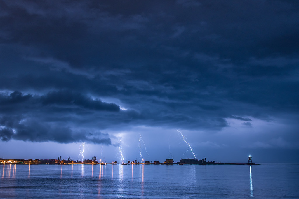 """WEDNESDAY, JANUARY 25, 2017<br /> <br /> LIGHTNING 9056<br /> <br /> """"Harbor Storm""""<br /> <br /> Today I'm thinking back to August 28, 2015.  A night when an incredible series of thunderstorms rolled across northeast Minnesota.  The storms made for an incredible lightning show over the harbor in Grand Marais.  I had checked the weather and saw an alert for a """"Severe Thunderstorm"""" warning.  Grand Marais has one of the few places in the county where you can safely photograph the lightning from under a large covered picnic shelter, so I decided to drive to town to try and catch the storms.  <br /> <br /> As I was driving south along Highway 61 the storms hit and the rate of rainfall was amazing.  I had to slow down to 30 miles per hour at times because the rain was hitting the road so hard it was difficult to tell where the lines on the road were.  I was a little worried that I was going to miss the lightning in Grand Marais, but thankfully the storms lasted for several hours and I was able to get quite a few good shots from the safety of the picnic shelter.<br /> <br /> Camera: Nikon D750<br /> Lens: Nikon 24-120mm f/4<br /> Focal Length: 38mm<br /> Exposure Time: 9.6 seconds<br /> Aperture: f/10<br /> ISO: 200"""