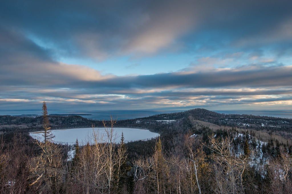 """SUNDAY, JANUARY 29, 2017<br /> <br /> LAKES 05052<br /> <br /> """"January Sunset over Teal Lake and Lake Superior""""<br /> <br /> Grand Portage, MN - Yesterday afternoon I went for a fat bike ride through some of the most mountainous terrain in northeast Minnesota.  There are several awesome views along the route that I took but this one is the best.  The circular lake you can see is called Teal Lake and beyond that is Lake Superior.  Resting on the horizon on the left side of the photo is Isle Royale National Park.  The peak to the right of Teal Lake is Mt. Josephine.  Our home is just on the other side of Mt. Josephine, right along the shoreline of Lake Superior.  What an amazingly beautiful place to call home!<br /> <br /> Camera: Sony DSC-RX100M3<br /> Focal Length: 24mm<br /> Exposure Time: 1/400<br /> Aperture: f/4<br /> ISO: 200"""
