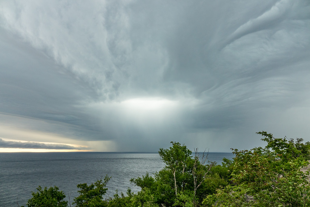 "WEDNESDAY, JUNE 14, 2017<br /> <br /> SUPERIOR SUMMER 04691<br /> <br /> ""Summer Storm over Palisade Head""<br /> <br /> Yesterday while driving home from Duluth the sky was incredible as a storm approached from the west.  At first, as we were driving between Duluth and Two Harbors, all we could see behind us was a big black wall of clouds approaching.  As we got a little further up the shore the clouds starting taking on all these incredible shapes and textures.  <br /> <br /> We stopped at the Palisade Head overlook in Tettegouche State Park to take some pictures of the sky.  During that time there was a rain squall occurring over the lake, with a brighter patch of light emanating from the center of the squall.  We only had a few minutes to enjoy the view before the heavy rain hit.  We were driving the rest of the way home in some pretty heavy downpours.<br /> <br /> Camera: Sony DSC-RX10M3<br /> Focal Length: 24mm<br /> Exposure Time: 1/125<br /> Aperture: f/4<br /> ISO: 200"
