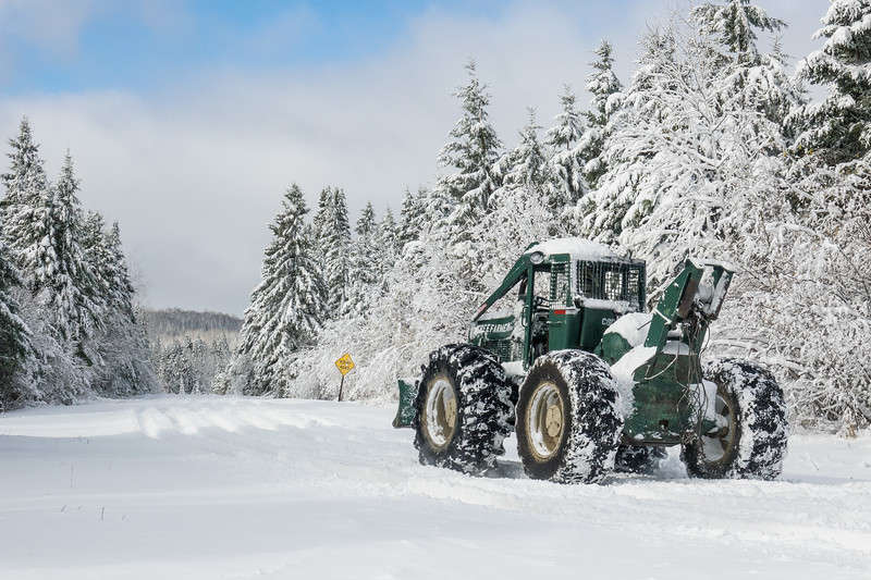 """THURSDAY, NOVEMBER 2, 2017<br /> <br /> TRANSPORTATION 06981<br /> <br /> """"Skidder on Old Highway 61""""<br /> <br /> I got pretty excited the other day when I was driving along Old Highway 61 in Grand Portage and saw this skidder coming down the road.  I pulled over right where there is an intersection and waited for the machine to get closer.  When it got to the intersection it turned and went West on the Old Highway.  It made for a great shot with the quarter view of the skidder flanked by the snow covered trees on both sides of the road.<br /> <br /> Camera: Sony DSC-RX10M3<br /> Focal Length: 77mm<br /> Exposure Time: 1/2500<br /> Aperture: f/5.6<br /> ISO: 200"""
