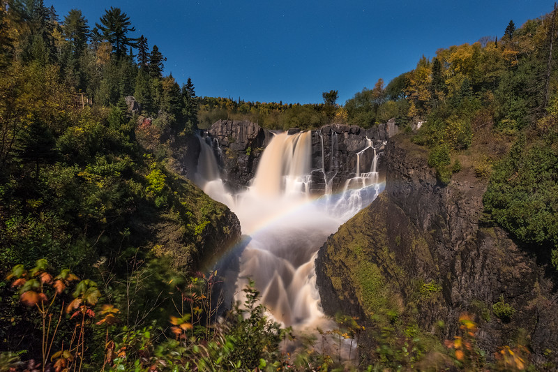 "FRIDAY, OCTOBER 6, 2017<br /> <br /> PIGEON RIVER 0408<br /> <br /> ""October Moonbow at High Falls""<br /> <br /> The moonlight last night sure was beautiful!  I went for a walk up to High Falls at Grand Portage State Park to see if there would be a moonbow.  Earlier this week we got several inches of rain which brought the water level in the river up about 4 feet.  When high water level coincides with full moonlight you can usually see a rainbow at night, often referred to as a moonbow.  <br /> <br /> As I walked up the trail the light from the moon was so bright I didn't even need to use my headlamp, even when I was beneath the forest canopy.  When I got my first glimpse of the falls I could easily see that there was indeed a rainbow visible at the base of the waterfall!  Such a cool and unique thing to see.  The wonders of this world are endless!<br /> <br /> Camera: FUJIFILM X-T2<br /> Lens: FUJINON XF 14mm f/2.8<br /> Focal Length: 14mm<br /> Exposure Time: 15 seconds<br /> Aperture: f/4<br /> ISO: 1600"