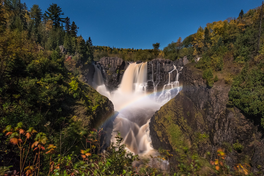 """FRIDAY, OCTOBER 6, 2017<br /> <br /> PIGEON RIVER 0408<br /> <br /> """"October Moonbow at High Falls""""<br /> <br /> The moonlight last night sure was beautiful!  I went for a walk up to High Falls at Grand Portage State Park to see if there would be a moonbow.  Earlier this week we got several inches of rain which brought the water level in the river up about 4 feet.  When high water level coincides with full moonlight you can usually see a rainbow at night, often referred to as a moonbow.  <br /> <br /> As I walked up the trail the light from the moon was so bright I didn't even need to use my headlamp, even when I was beneath the forest canopy.  When I got my first glimpse of the falls I could easily see that there was indeed a rainbow visible at the base of the waterfall!  Such a cool and unique thing to see.  The wonders of this world are endless!<br /> <br /> Camera: FUJIFILM X-T2<br /> Lens: FUJINON XF 14mm f/2.8<br /> Focal Length: 14mm<br /> Exposure Time: 15 seconds<br /> Aperture: f/4<br /> ISO: 1600"""