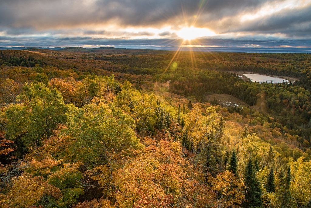 "THURSDAY, SEPTEMBER 28, 2017<br /> <br /> AUTUMN 3130<br /> <br /> ""Good Morning Northwoods!""<br /> <br /> Yesterday morning's sunrise over the Grand Portage forest in northeast Minnesota.  It was so cloudy we weren't sure the sun was going to peek out but it eventually did a few times.  During one of those brief moments I made this photograph and happened to catch a really nice lens flare too.  The fall colors are a little weird this year.  So many of the leaves seem to just be turning brown rather turning a nice vibrant color.  Still, the forest is always a beautiful place to be even if the colors aren't prime this year :-)  <br /> <br /> Camera: Nikon D750<br /> Lens: Nikon 24-120mm f/4<br /> Focal Length: 24mm<br /> Exposure Time: 1/25<br /> Aperture: f/11<br /> ISO: 200"