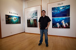 "Eric Cheng posts with his aluminum prints at ""H20"", The G2 Gallery"