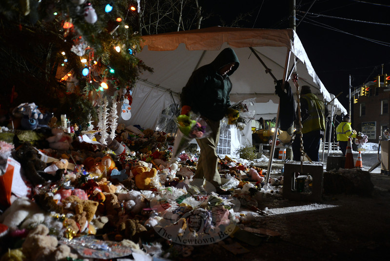 Since 11 pm on Friday, December 28, and into the predawn hours of December 29, town crews cleared the accumulation of gifts, poems, toys, stuffed animals, candles, and more that flooded Sandy Hook in an outpouring of grief and support. At approximately 3:30 am on Saturday, the Sandy Hook School memorial site near the Sandy Hook Volunteer Fire Company garage on Riverside Road, which included decorated Christmas trees, had been cleared and town personnel had begun work in Sandy Hook Center. As the new day approached, just a few men remained to reclaim sidewalks near The Glen at the corner of Church Hill Road and Washington Avenue, and adjoining areas where the memorial offerings had spread. With a row of large industrial packing boxes quickly filling, the crew moved bundles of toys and animals, placing them in waiting boxes. (Bobowick photo)
