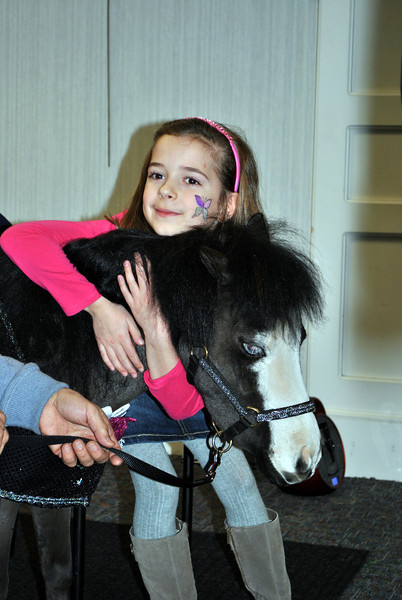 Audrey Nichols, 8, gives Magic a big hug during the special Gentle Carousel program at the C.H. Booth Library, Saturday, January 5. (Crevier photo)