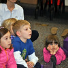 From left, Olivia Bragoli and Conrad Chapman, sit attentively during the reading of a story at the library, January 5, while Kathryn Lynders sprawls on the floor nearby. Cristina Lynders, Kathryn's mother, listens, too. (Crevier photo)