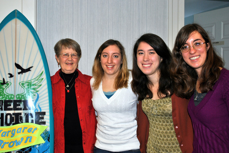 Visiting with outgoing young adult librarian Margaret Brown, left, at her retirement party on January 4, were three of the earliest members of the Young Adult Council (YAC) Ms Brown initiated. From left are Christine D'Alessandro, Victoria Mead, and Heather Smith, all members of the Newtown High School Class of 2009. The surfboard next to Ms Brown emphasized the staff's happiness for her next phase in life — a long trip to Hawaii. (Crevier photo)