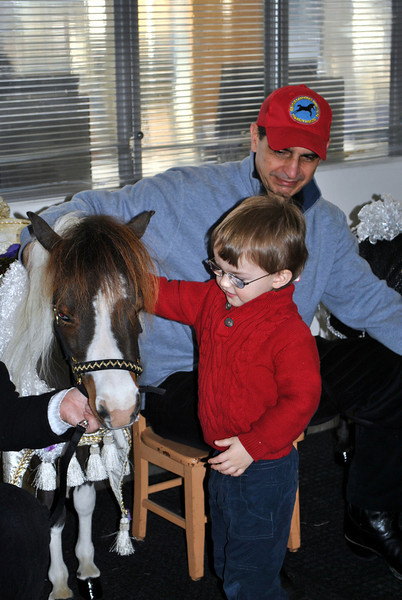 Fraser Woods student Charlie Wermuth is happy to pet therapy horse Wakanda. Gentle Carousel Miniature Therapy Horses co-founder Jorge Garcia looks on. (Crevier photo)