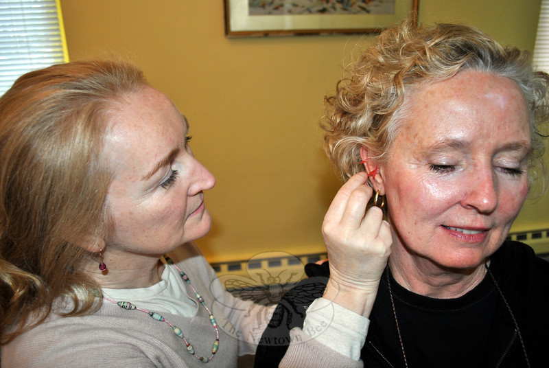 Acupuncturist Regina Walsh, president of Connecticut Society of Acupuncture & Oriental Medicine, places needles into the ear of Patricia Ryan. Acupuncture needles placed strategically in the ear are said to relieve stress. Ms Walsh and 50 other licensed acupuncturists are operating out of the former Mr Turtle's School in Sandy Hook Center, offering free acupuncture to anyone in need.	(Crevier photo)