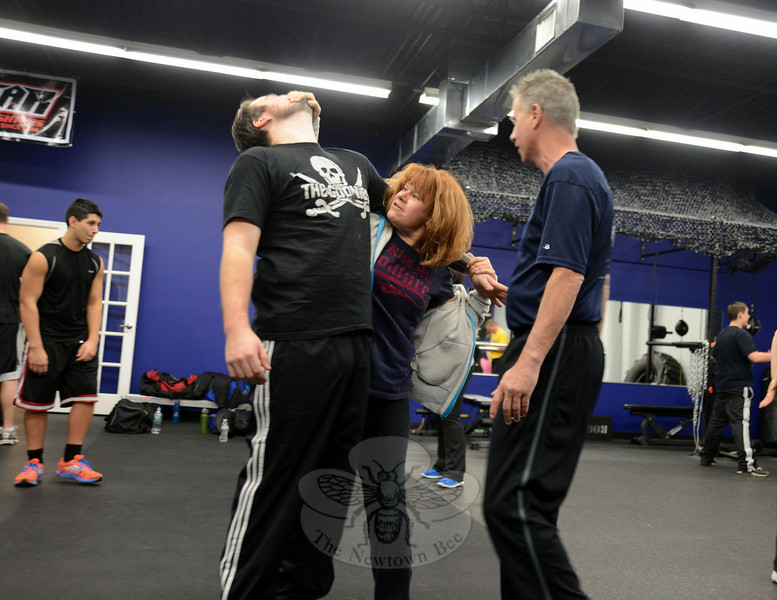 Tasha Williams, one of the many Krav Maga students at the Cannon Ridge Training Center on Simm Lane this week, practices her defense moves on Gordon Johnson. Observing them is Chris Anderheggen. (Bobowick photo)