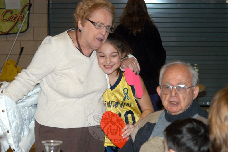 Newtown Youth Basketball Association player Jillian Carrino gives a flower to Kay Egan during a spaghetti dinner and early Valentine's Day celebration for senior citizens at Newtown High School on February 1. Also pictured is attendee Walt Boland. (Hutchison photo)