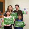 "Tim Stan created green and white We Are Sandy Hook / We Choose Love signs within days of 12/14 as a therapeutic release for himself and fellow residents. It has become a popular message, appearing around town and the region. Newtown will not be defined only by ""this horror that came to us,"" he said. His is a positive, defiant message, he feels. With Mr Stan is his wife Julie, and their children Katie and Eli. (Hicks photo)"