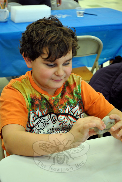 Photo right, 8-year-old Jackson Brunetti of Newtown forms clay into a shape to be used in constructing a Ben's Bell pendant. The Tuesday afternoon workshop was the first of several workshops scheduled to be held at HealingNewtown Arts Space on Queen Street. Ben's Bells crafted in workshops will initially be hung around Newtown, joining 1,000 others distributed in January, but volunteers are encouraged to hang a Ben's Bell wherever random acts of kindness are needed. Ben's Bells are never sold, only discovered. For information on future workshops, visit healingnewtown.org. (Crevier photo)