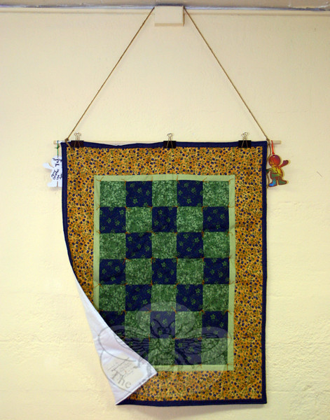 """This year's pancake supper not only offered dinner for hundreds of guests, but also offered the opportunity to see some of the art, quilts, plaques, and other items that have been sent to St John's since 12/14. This quilt was a gift, """"with prayers of hope and God's blessings,"""" according to a tag on its reverse, from The St John's Prayer Quilt Guild in Oneida, N.Y. (Hicks photo)"""