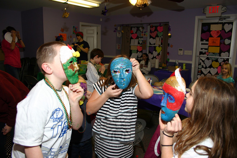The Sandy Hook Arts Center for Kids (SHACK) hosted Fat Tuesday Mask & Merry Making fun on February 12. Children who participated were invited to decorate masks with paint, feathers, beads, pipe cleaners, and other decorative accessories. Hiding behind these three very colorful masks are, from left, Joseph Doherty, Alexa Unger and Camille Paradis. Between mask making, participants enjoyed pizza dinner from figs, New Orleans-style music and more painting. (Hicks photo)