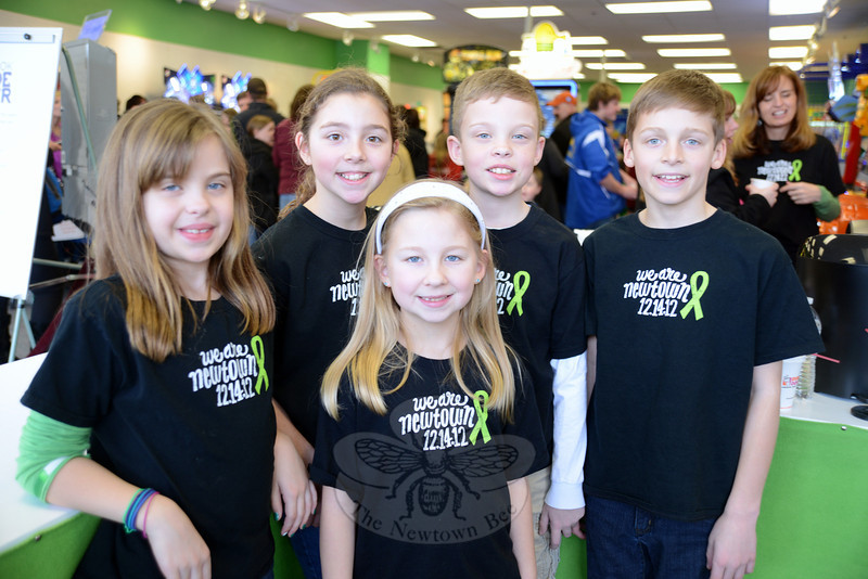 From left are Jillian Clure, Hannah and Rachel Cicciari, Tyler Clure, and Andrew Cicciari, welcoming guests to the arcade that their fathers Andrew Clure and Scott Cicciari recently opened. Children and adults maneuvered controls translating moves to onscreen race cars and motorcycles Saturday, February 16, during the grand opening of Newtown's new Sandy Hook Arcade Center (SHAC), which has sprung up in record time in Sand Hill Plaza, 228 South Main Street.  (Bobowick photo)