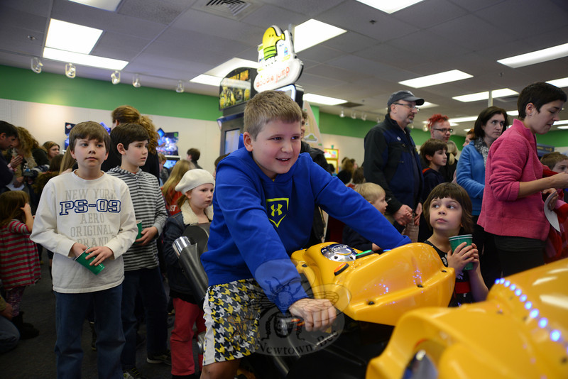 Grant Baker rides the motorcycle at Super Bikes 2. Children and adults maneuvered controls translating moves to onscreen race cars and motorcycles Saturday, February 16, during the grand opening of Newtown's new Sandy Hook Arcade Center (SHAC), which has sprung up in record time in Sand Hill Plaza, 228 South Main Street. (Bobowick photo)