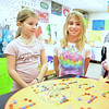 Anneliese Altimari, left, and Molly Moran took at projects celebrating the number 100, including the 10+10+10 on the table below, for Middle Gate Elementary School's 100th day of school celebration, held on Wednesday, February 20. (Bobowick photo)