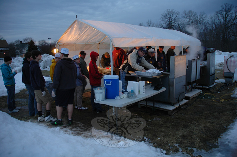 Members of the Knights of Columbus worked outdoors under shelter on the evening of Friday, February 22, to prepare fried fish filets for the annual Friday Knight Fish Fry at St Rose of Lima Church. The event also will be held on March 1 and March 15, with free dinners being offered to first responders who show their IDs on the final night of this year's Lenten offering. This year, in addition to fried fish, the Knights have added baked fish with a white wine reduction to the menu, which also includes macaroni and cheese. Dinners include french fries and homemade coleslaw, dessert and soft drinks. Continuing clockwise: At the fish fryer, Knight Len Moritz displays a fried filet of tilapia, a freshwater food fish that makes for a tasty meal; a tray of tilapia filets is shown after being removed from a fryer; and at the serving tables in the St Rose Church Parish Hall, servers provided freshly prepared fish dinners to  guests on February 22. Friday Knight Fish Fry events run from 5 to 8 pm. Cost is $8 for adults, $5 for children, and $26 maximum for families (eat-in only). Takeout orders are also available. (Gorosko photo)
