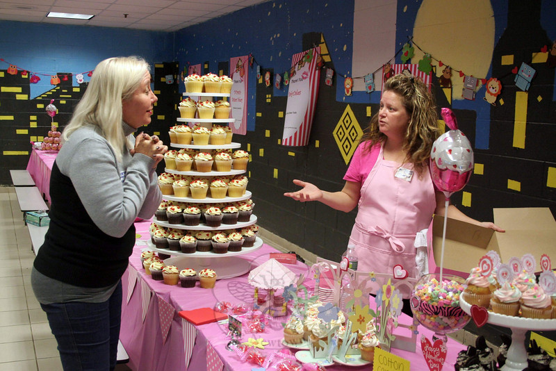 "The Newtown High School cafeteria was turned into a confectionary gathering spot on Valentine's Day. Vikki Grodner, founder of Life is Precious, traveled from Alabama to help deliver thousands of cupcakes to Newtown's first responders, the immediate families of those who lost loved ones on 12/14, and the children of Sandy Hook School. The offering was Mrs Grodner's way of ""giving the community communal hugs,"" she said. Cupcakes from five bakeries, a few hundred cupcakes from Walmart and Sam's Club, and cookies from DOrazio Sisters were all set out for a few hours. Walmart also provided arts and crafts supplies for the youngest visitors, encouraging them to create valentines or whatever their heart desired. ""People were so taken with the fact that we did this,"" said Mrs Grodner, shown here with Deputy Land Use Director Rob Sibley. ""It was a huge success,"" Mrs Grodner said the following morning. Mr Sibley, who is also an engineer with Sandy Hook Volunteer Fire & Rescue, was one of the town employees who helped organize the event. (Hicks photo)"