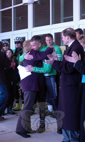 First Selectman Pat Llodra hugs Chris McDonnell, Team 26 rider and father of Grace McDonnell, one of the student victims on 12/14, at a rally held at Reed Intermediate School on Saturday, March 9, to send off Team 26 on a 400 mile cycling journey to Washington, D.C. (Hallabeck photo)