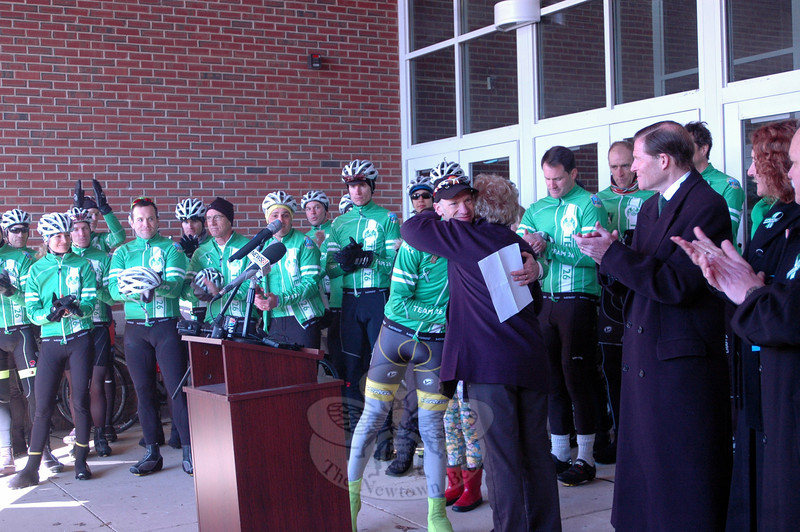 Team 26 organizer Monte Fank hugs First Selectman Pat Llodra at a rally held at Reed Intermediate School on Saturday, March 9, to send off Team 26 on a 400 mile cycling journey to Washington, D.C. (Hallabeck photo)