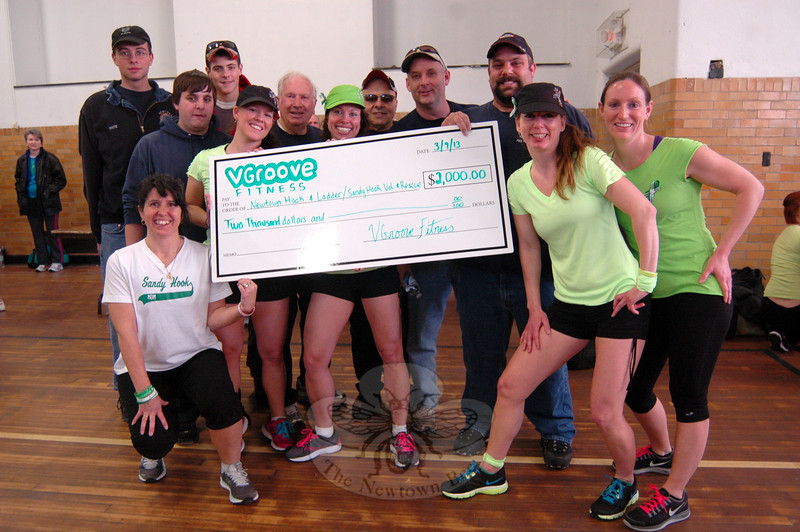 """VGroove Fitness """"Shake It For Sandy Hook"""" Cardio dance fundraiser organizers presented members of Sandy Hook Volunteer Fire & Rescue and Newtown Hook & Ladder Co. #1 a $2,000 check on Saturday, March 9, in the gymnasium at Edmond Town Hall. (Hallabeck photo)"""