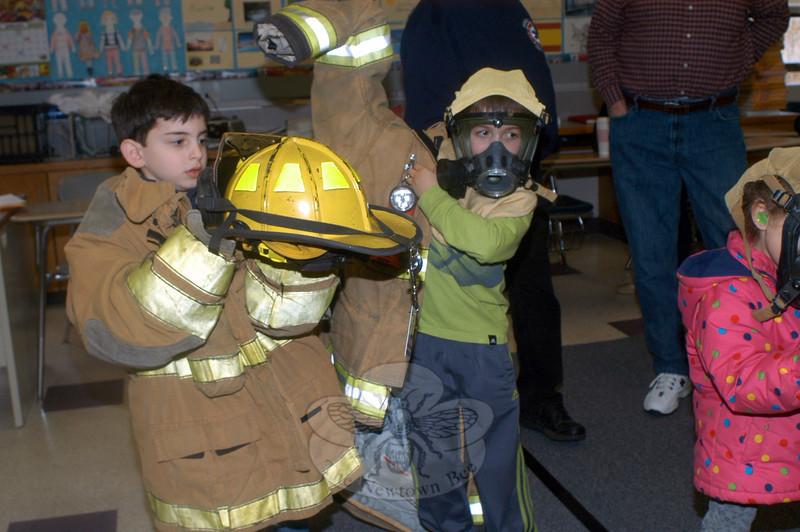 Sam Stoltz, left, and Ryan Zaniewski try on Sandy Hook Volunteer Fire & Rescue uniforms. (Hutchison photo)