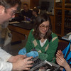 Instructor Trent Harrison demonstrates some careful squid dissection methods to Shari Paley and her son Ethan Paley (appropriately dressed with a squid hat). Ethan's brother, Benjamin, and their dad, Andrew, also attended. (Hutchison photo)