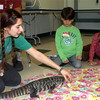 Wendy Mumford, assistant naturalist from the North Salem, N.Y.-based The Nature of Things, shows young learners, including Andrew Rosa and Katie Nichols, a Argentine Tegu lizard named Ralphie. (Hutchison photo)