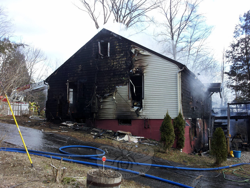 As flames and smoke enveloped a wood frame house on March 27 on Berkshire Road, local volunteers climbed to the roof with a chainsaw to vent the smoke and flames from the attic. (Voket photo)