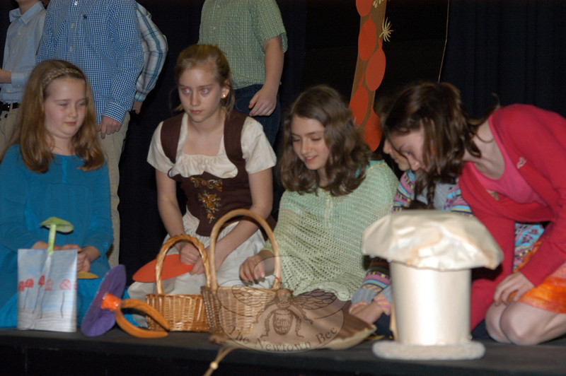 Emily Stringer, Monika Mikok, Kira Schoenberg, and Pauline Fernandez are among the students showing the audience how chocolate is made during the Housatonic Valley Waldorf School Language Assembly at Newtown Middle School on March 23. (Hutchison photo)