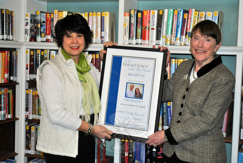 Newtown Labor Day Parade Committee President Beth Caldwell, left, presents a framed copy of the 2012 parade program to C.H. Booth Library Director Janet Woycik, Thursday, March 28. The image will be displayed near the main circulation desk, along with framed programs from the past gifted to the library, in the weeks just prior to the September 2 Newtown Labor Day Parade, says Ms Woycik. (Crevier photo)