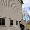 Robert and Jane Cottingham are dwarfed by the main barn that sits on their property at 12-16 Blackman Road. The farm was recently named to the State Register of Historic Places, along with an-other farm on Berkshire Road. (Crevier photo)