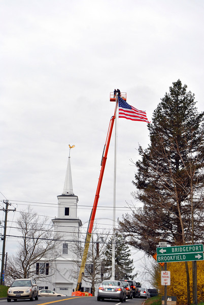Paul Bastiaanse and Dan Hern of Valley Restoration in Torrington were above it all, Tuesday morn-ing, April 16, as they repaired the stem and set a new gilded ball in place on the flagpole. The gilded ball that formerly topped the flagpole was lost last August when a truck hit the pole, knocking the ball off its post. Despite a search in the area at that time, the 16-inch-diameter ornament was never recov-ered. Renovations to the flagpole are usually funded by efforts of retired Newtown Police lieutenant David Lydem. (Crevier photo)