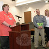 Newtown Director of Emergency Communications Maureen Will, at podium, speaks April 17 at an awards ceremony at Newtown Municipal Center at which local Dispatcher Bob Nute, center, was named the national winner in the Second Annual Smart Telecommunicator Awards. At right is Mr Nute's wife, Susan. (Gorosko photo)