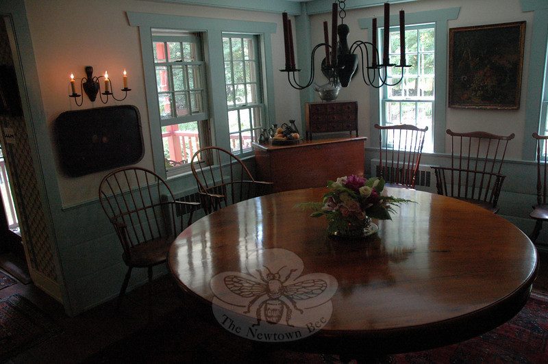 A floral centerpiece accents a circular table , which is the central piece of furniture in a dining room at the Taylor-Fries residence in Sandy Hook during the 17th Annual Newtown Historical Society House & Garden Tour. (Gorosko photo)