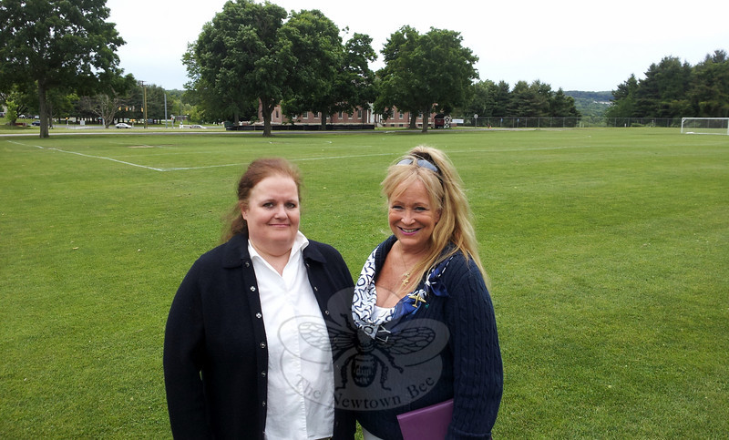 Una Lucey, left, and Wendy Lee Hewitt, co-organizers of The Great Newtown Reunion, stand on the site of the planned July 27 event. Tickets for the all-day and evening festivities are on sale now for $65. (Voket photo)