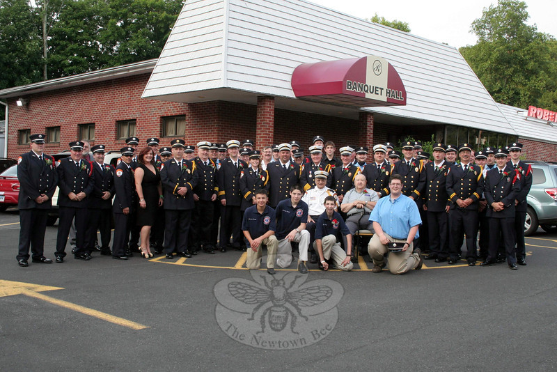 "Members, family and friends of Sandy Hook Volunteer Fire & Rescue gathered at Roberto's in Monroe on Saturday, June 22, to celebrate the 75th anniversary of the fire company. Special guests included members of each of Newtown's additional fire companies, the Board of Fire Commissioners members, and chiefs and members from neighboring towns. Fire Commissioner Kevin Cragin served as emcee for the event, which included special honors for company members reaching different points of service, ranging from five to 65 years of service. Mike Lucas and Richard Andrews were honored for service of more than 60 years each. Special honors were also presented to the top ten responders during the past five years, the ladies auxiliary and its members were celebrated, and Chief Bill Halstead was thanked for leading the company for the past 35 years. In a departure from tradition, the Member of the Year Award was announced during the event rather than during the annual company meeting earlier in the month. Committee members Kenneth Carlson, Chuck Kilson and Steve Stohl announced that instead of the award going to one person, the honor this year was to be shared by all members of the company — officers, firefighters, fire police, ladies auxiliary and Junior Corps — for the work shown by all ""on an extremely shocking day in December,"" and in the weeks that immediately followed. (Hicks photo)"