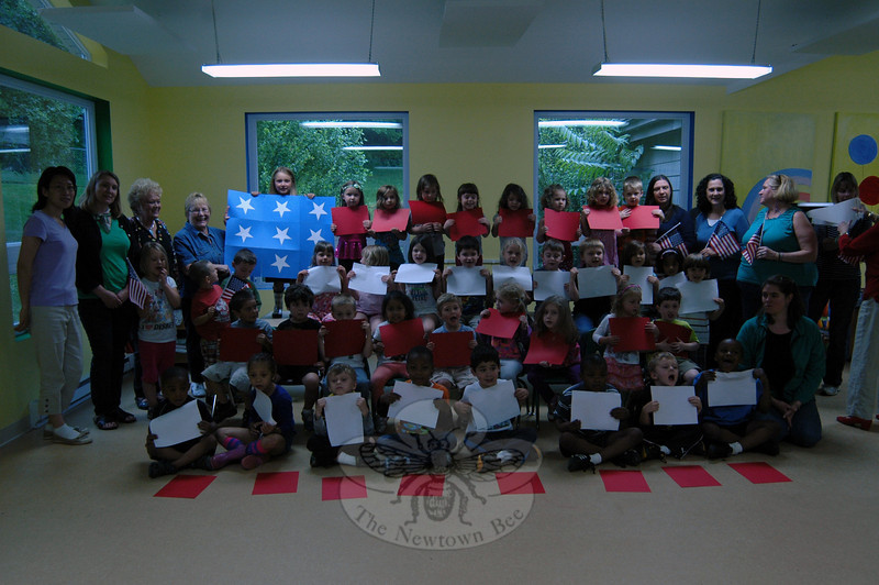 """To celebrate Flag Day, recognized on June 14, and prepare students for the day, the Children's Adventure Center gathered its preschoolers together on Thursday, June 13, to form a """"flag"""" with the help of colored paper, stars, and Children's Adventure Center staff.  (Hallabeck photo)"""